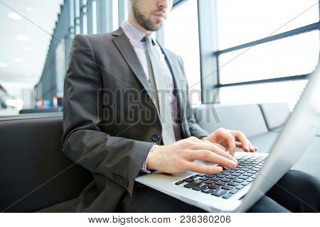 Contemporary agent with laptop on knees browsing in the net while waiting for his flight