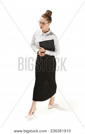 Full Length Portrait Of A Smiling Female Teacher Holding A Folder Isolated Against White Background.