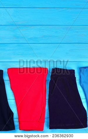 Kids Shorts Collection, Copy Space. Set Of Fabric Colored Short Pants For Kids, Blue Background. Bab