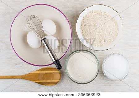 Oat Flour, Bowl With Chicken Eggs And Whisk, Sugar, Salt, Bamboo Spoon On Wooden Table. Top View