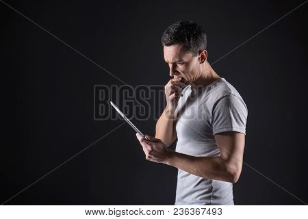 Thoughtful Look. Smart Pleasant Thoughtful Man Standing With A Tablet In His Hand And Holding His Ch
