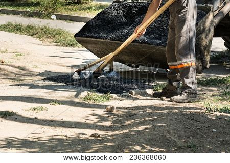 Road Repair Details. The Worker Levels The Hot Asphalt With A Wooden Device.