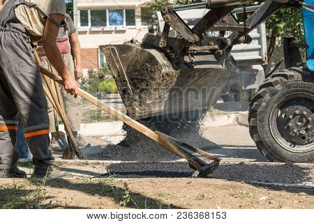 Road Repair Details. The Worker Levels The Hot Asphalt On The Sidewalk.