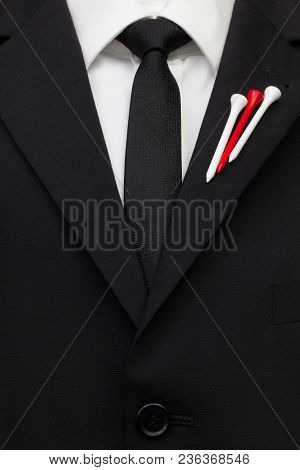 The Detail Of Wedding Suit With Golf Design. Blue Golf Tees On The Flap Of Black Jacket.