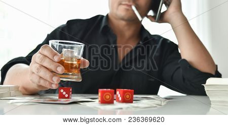 Gambling Concept. Alcohol Addicted Asian Man In Black Shirt With Dice, Cigarette And Whiskey Glass.