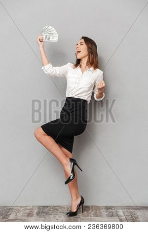 Photo of excited young business woman standing isolated over grey wall background make winner gesture holding money.