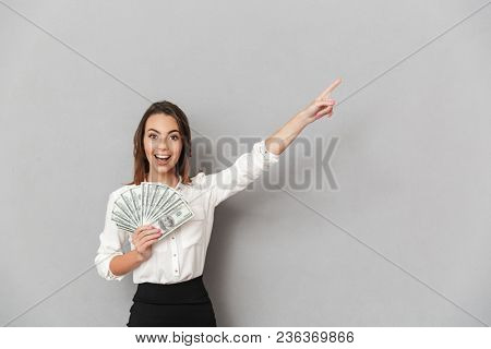 Image of excited cheerful young business woman standing isolated over grey wall background looking camera holding money pointing.