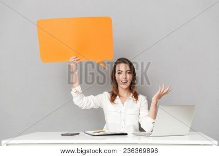 Image of an amazing happy young business woman sitting isolated over grey wall background using laptop computer holding speech bubble.