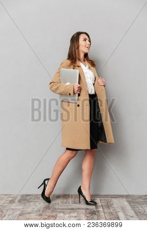 Image of happy young business woman standing isolated over grey wall background holding laptop computer looking aside.