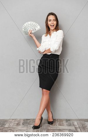 Photo of excited cheerful young business woman standing isolated over grey wall background looking camera holding money.