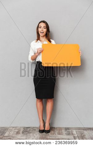 Image of emotional young business woman standing isolated over grey wall background holding speech bubble.