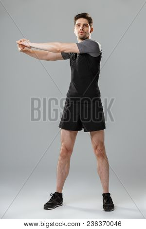 Full length portrait of a motivated young sportsman warming up isolated over gray background