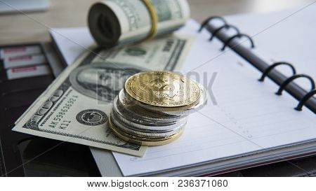 Golden Bitcoins On Top And On A Us Dollar And Notebook. Bitcoin Crypto Currebcy On Us Dollars. Virtu