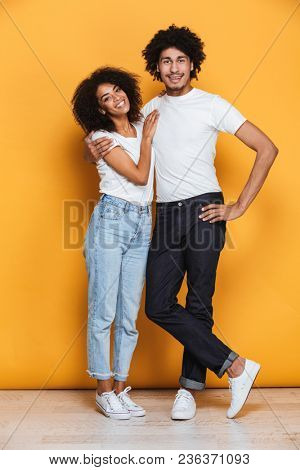 Full length portrait of a happy afro american couple hugging isolated over yellow background