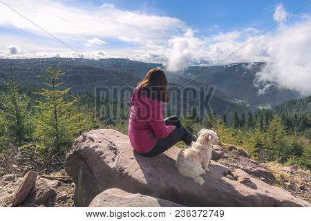 Young Brunette Woman With Her Bichon Havanese Dog Sitting On A Rock Admiring The Hornisgrinde Mounta