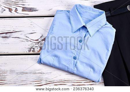 New Folded Light Blue Girls Shirt. New Formal Shirt And Black Skirt For School Girl Close Up. High Q