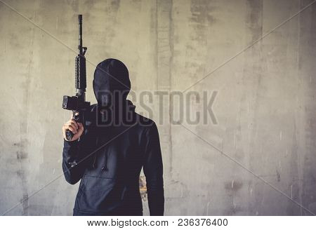 Terrorist Holding Rifle Gun On Grunge Wall. Social Issued Theme. Terrorist And Robber Concept. Polic