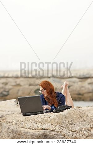 College Girl Studying Using Laptop on Jetty Rocks