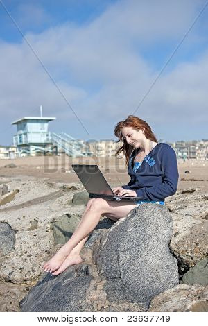 Young Woman Happily Using Laptop at Beach
