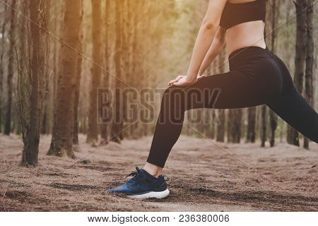 Close Up Of Lower Body Of Woman Doing Yoga And Stretching Legs Before Running In Forest At Outdoors.