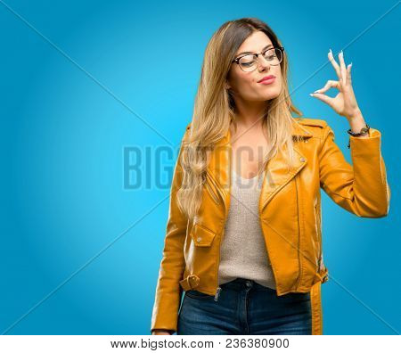 Beautiful young woman doing ok sign with hand, approve gesture, blue background