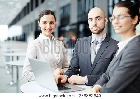 Group of young contemporary business people with laptop networking in lobby of airport before departure