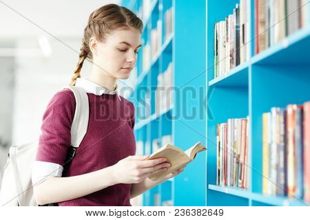 Clever student with backpack looking through book while standing by shelf in college library