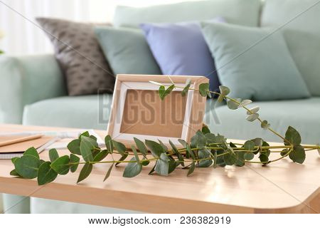 Wooden table with frame and twigs in living room