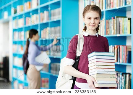 Clever girl with stack of books and rucksack standing by bookshelf and looking at camera