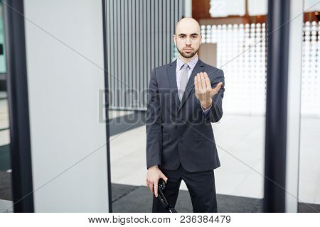 Serious airport security in formalwear showing come here gesture to someone while inviting for check procedure