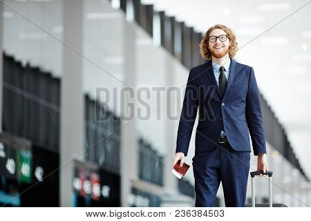 Happy business traveler with baggage and passport walking to check-in counter of airport before departure