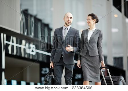 Young business travelers with baggage having talk while walking to check-in reception or exit