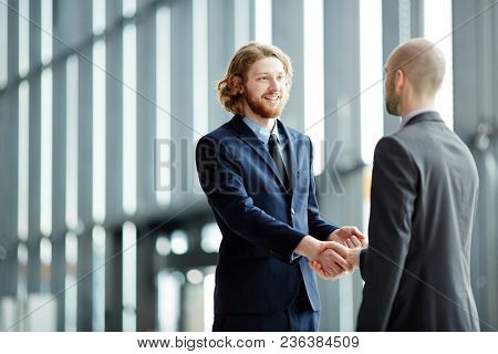 Two young businessmen in suits greeting one another by handshake after confirming deal