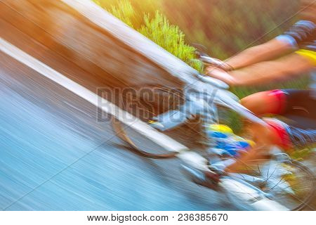 Slow motion photo of a sportsman riding on the bicycle along the mountainous road in Alps, almost on the finish line, athletic summer, enjoying workout, bicycle tour to Italy