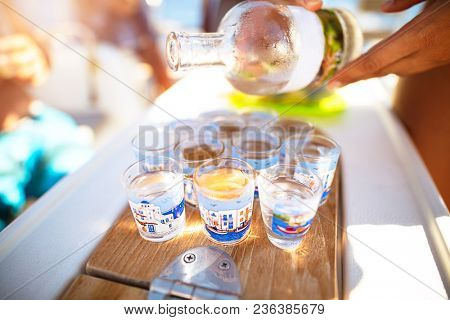 Party on the beach, refill glass with alcoholic beverage, drinking shots with friends, enjoying freedom, happy carefree summer vacation
