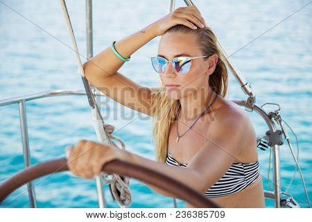 Portrait of a beautiful blond woman on sailboat, attractive young captain, active summer vacation, marine fashion look, youth lifestyle