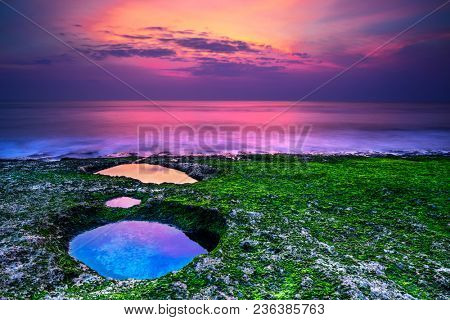 Beautiful landscape of an amazing purple sunset over the sea, majestic view of Padang Padang beach in the evening, Bali, Indonesia