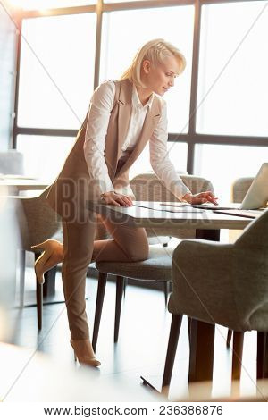 Young elegant manager in smart casual leaning over table with laptop while reading information in the net