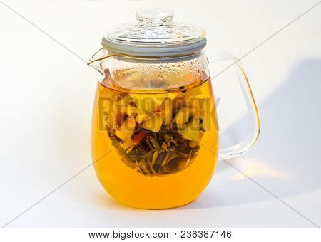 Green tea with ginger and spices. In a transparent teapot. Healthy eating. With three balls of green tea poster