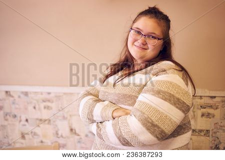 Portrait Of Beautiful Chubby Caucasian Woman Standing In Front Of A Two Toned Wall With Decorated Wa