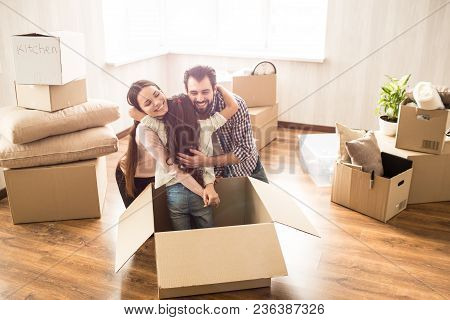 Cheerful Young Parents Are Hugging Their Daughter Together. They Have Found Her In A Box. She Hided