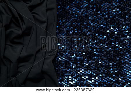 dark background of black fabric and blue shiny pieces