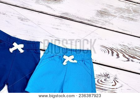 Kids Summer Colored Shorts. New Kids Cotton Shorts On White Wooden Background. Childs Casual Outfit