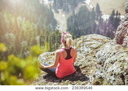 Young Girl Traveler Sits On Top Of A Mountain In A Yoga Pose. The Girl Loves To Travel. Concept For