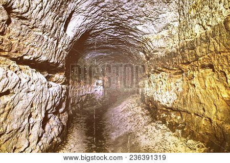 Abstract.  The Old Sandstone Water Tunnel, Mined Caves.  The Cave. Sandstone Tunnel Moistened Walls.