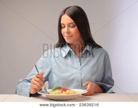 Beautiful woman eating spaghetti