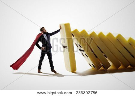The Man Stops The Falling Dominoes. Concept Of Crisis Management.