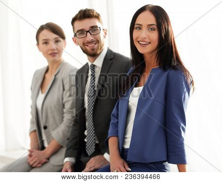Business woman smiling with her colleagues in the background