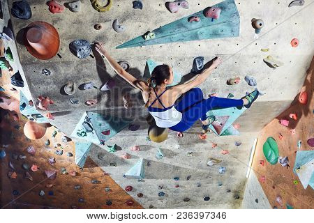 Workout Exercise. Woman Climber Climbs Indoors In Bouldering Gym. Young Woman Climbing Up On Practic