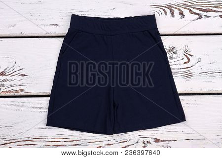 Baby Boy Classic Black Shorts. Toddler Boy Textile Casual Shorts, Old Wooden Background. Kids Summer